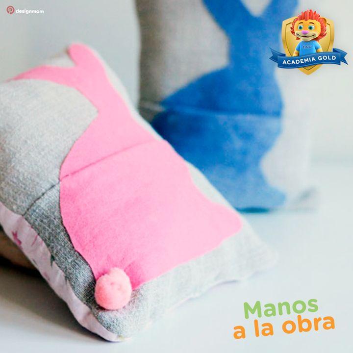 Si quieres decorar la cama de tus hijos de forma súper fácil y linda, recorta tela de pellón con la silueta de un par de conejitos y pégala a unos cojines con un pegamento especial para telas. Después cose un pompón y ¡listo!