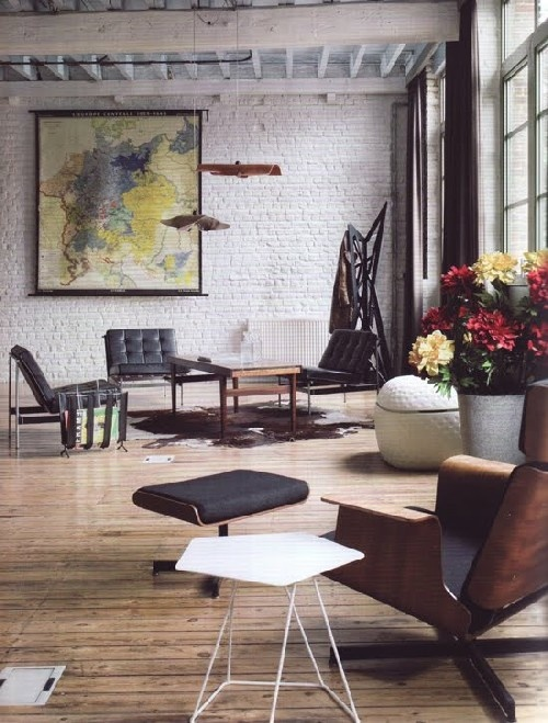 Wood floors, white walls, black/white/brown furniture, map on the wall