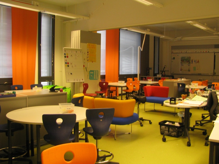 Ritaharju School, Oulu, Finland. Two classrooms with a mix of soft furniture and wheeled classroom chairs; bright colour scheme limited to furniture and curtain panels; folding doors to allow the class spaces to be separated into two rooms giving flexibility in use of space; light walls, floor and tables.