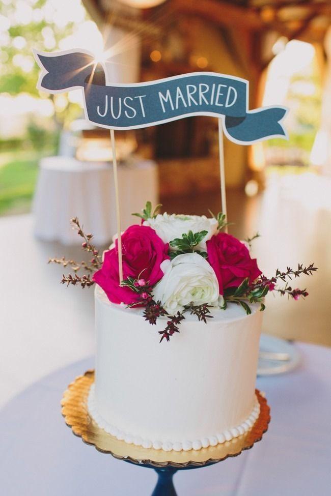 Flores y un cartel de recién casados decoran este simple pastel de bodas. Lauren Fair Photography