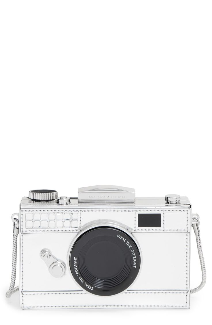 Stealing the scene with this silvery camera frame clutch from Kate Spade, lit up with crystals and a logo-engraved bow clasp. A drop-in chain strap makes crossbody styling a snap for versatile looks and styles.