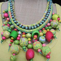 Ketting 2 rijen van zacht weefsel overwegend groen en roze, houten kralen, katoenen ballen bedekt met stof en zijde cocons