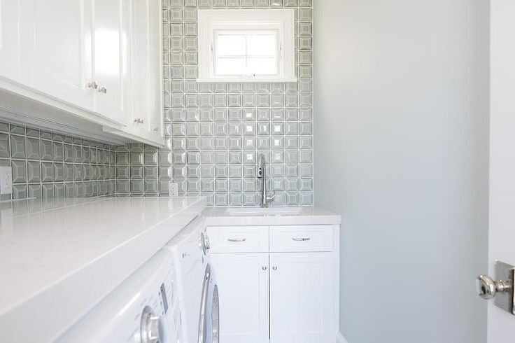 White and gray laundry room features white cabinets paired with white quartz countertops and a gray prism tile backsplash.