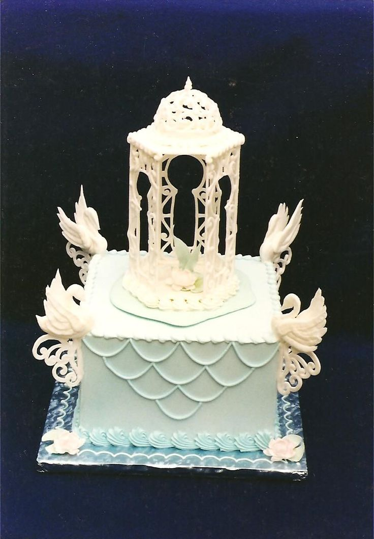 """Swan Gazebo - This was a competition cake. It may be hard to see in the picture, but inside the royal icing gazebo is a gumpaste water lily. The gazebo is resting on a run-sugar """"island"""", surrounded by hand piped royal icing swans. This was done a number of years ago, but i think i recall receiving a first place in the category as well as Best of Division for this entry. Thanks for looking!"""