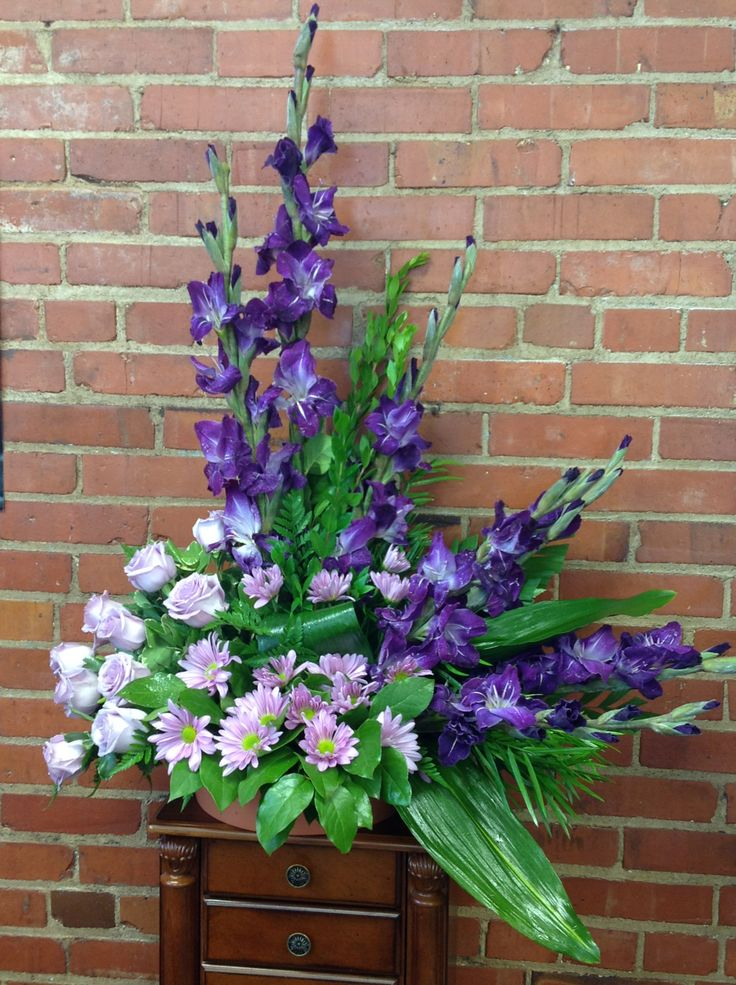 Purple glads, lavender daises and roses. Manly colors but could also be used for a lady.