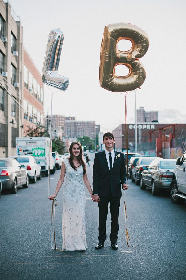 bride and groom holding silver and gold letter balloons | photo: www.levkuperman.com