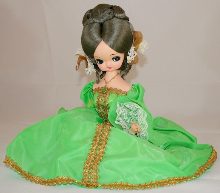 Bradley Import Company founded in 1954 in Los Angeles, California they imported dolls made in Japan and Korea, also called; Glamour Doll, Big Eyed Girl Dolls, foam with beige nylon over wire body, came in many different long gowns and other accessories and some were on a wood stand.  This one is dressed in an emerald green dress with gold braiding. She also has a green necklace. Legs are gracefully posed under this lady with the traditional silver lace slippers.  Cloth dolls are painted…