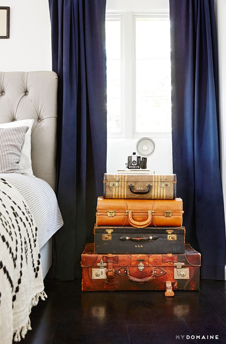 Navy curtains in bedroom with suitcases stacked as nightstand and vintage camera on top
