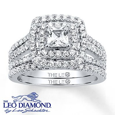 A fabulous princess-cut Leo Diamond at the center of her engagement ring is the highlight of this magnificent bridal set for her. Two rows of dazzling round diamonds frame the center and decorate the bands of the engagement ring and the matching wedding band. The central diamond is independently certified and laser-inscribed with a unique Gemscribe® serial number. The bridal set is styled in 14K white gold and has a total diamond weight of 1 1/2 carats. Diamond Total Carat Weight may ...