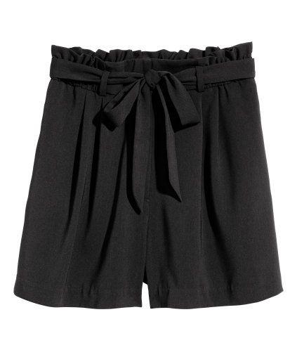Svart. Ett par korta shorts i vävd kvalitet. Shortsen har hög midja och lagda veck upptill. Sidfickor och knytskärp. Gylf med dragkedja samt hyska och hake.
