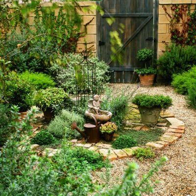 Old-World kitchen garden : Dining and gardening combine in this elegant potager where herbs and vegetables grow near the table. Herbs and edible plants grown in pot are cordoned off from the gravel path with a charming circular stone border.