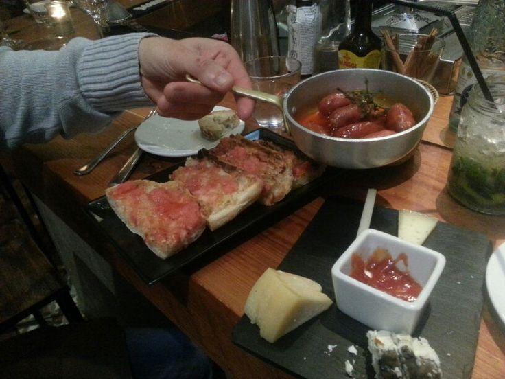 Restaurant Sensi gourmet tapas à Barcelone. Assortiment composé de chorizos au miel, de fromages catalans accompagnés de confiture, pain frotté a la tomate fraiche.