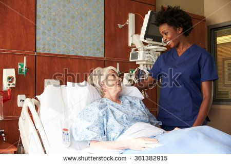 Nurse Talking To Senior Female Patient In Hospital Bed - stock photo