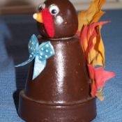 Turkey made from a clay flower pot and fall leaves (real or fake). Easy for kids to make.