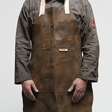 Leather Workshop Apron from The Rag And Bone Man.  Having destroyed more than a few workshop aprons Paul thought that it was time we made our own that would last.  Our leather workshop apron is made using distressed nappa leather that has a natural full grain. Knicks, burns, scars and marks all tell the story of this product's journey and accentuate its character. This softer leather is also very flexible, perfect for light and medium duty.