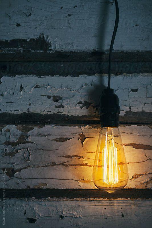 Edison light bulb on weathered rustic wood background.  Sean Locke for Stocksy United