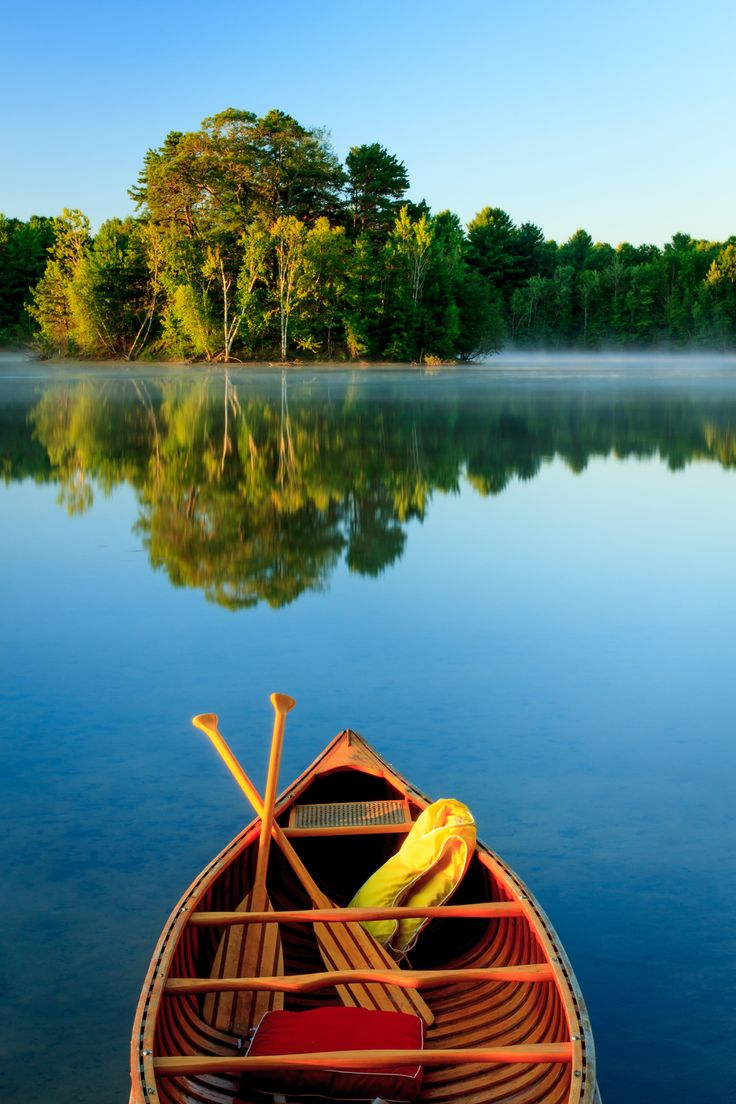 A wooden canoe on a peaceful lake looking over the reflections of a lush forest? Sign us up.