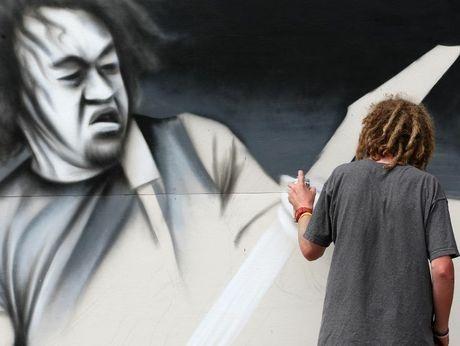 Owen Dippie in action painting a billboard of Laughton Kora in 2010.