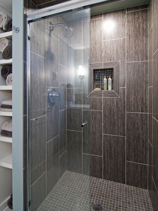 large tiles and possible half doortile placed vertically on wall that matches bathroom floor shower floor in mosaic tile that matches