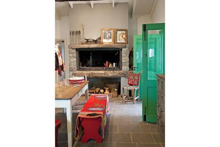 Tres casas con estilo campo  El comedor diario armado con una mesa vieja y bancos pintados de rojo se ubicó junto a un fogón con frente de piedra. Sostiene la puerta una silla santiagueña con manta bordada del NOA.