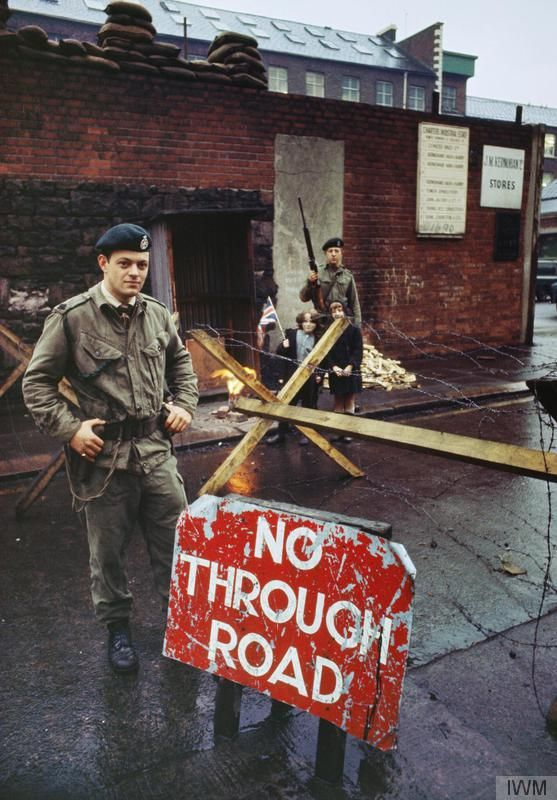 2nd Lieutenant Peter Hall of 1st Battalion, The Royal Green Jackets, at a road barricade on a wet winter's day in Belfast. A rifleman and two children equipped with Union Jack flags are in the background.