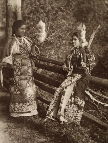 Teenage girls in embroidered dress spin flax fiber for thread. Romania, no further info