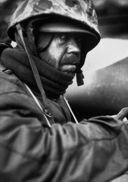 Weary, exhausted Marine, Jesse D. Place, huddles against the bitter cold during the retreat from Chosin Reservoir, Korea, winter 1950. Photographer David Douglas Duncan—Life Magazine