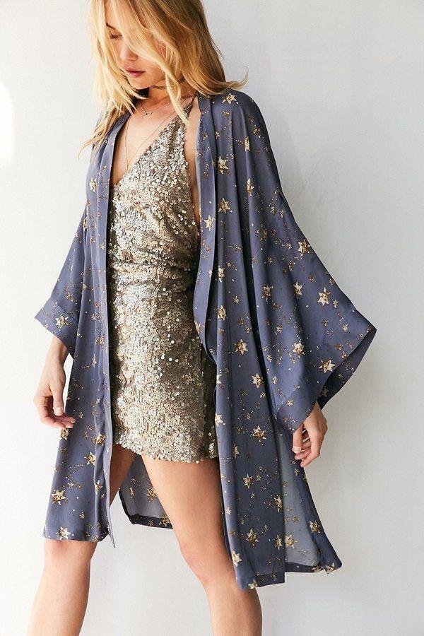Vestido de paetê dourado e kimono cinza azulado com estrelas brilhantes.