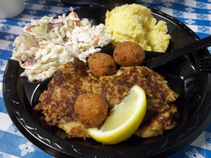 Crab cakes, cole slaw, hush puppies, and cheese grits from