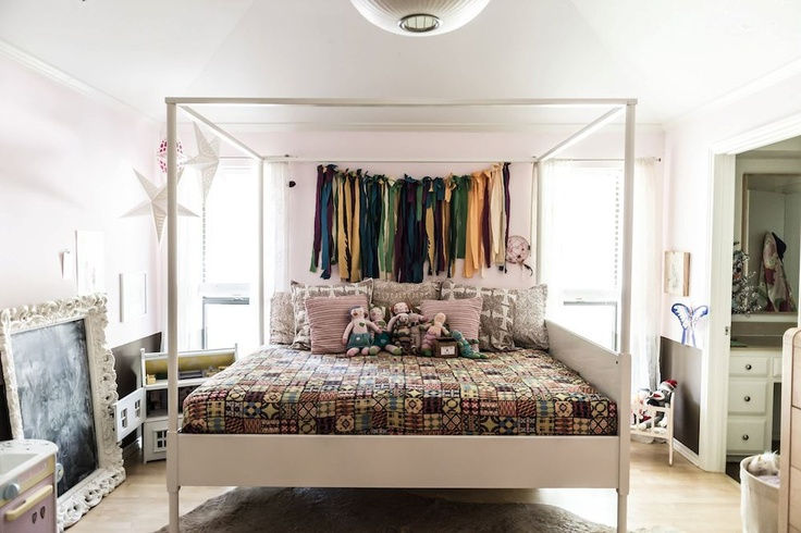 from Rue Magazine: band of ribbons above the bed in lieu of a headboard!