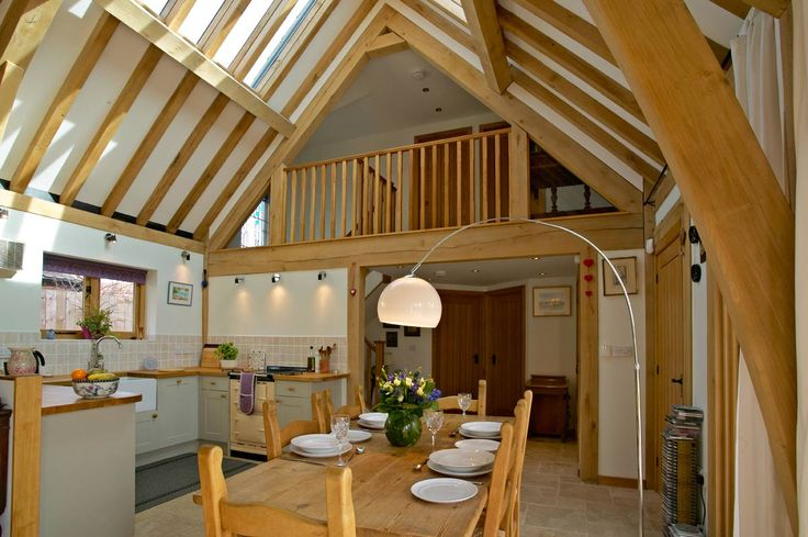 Beautiful one-and-a-half storey home from Welsh Oak Frame with open-plan, double height living area. The vaulted ceiling gives a more spacious look and feel with a gallery landing. #oakframe #vaultedceilings #openplan