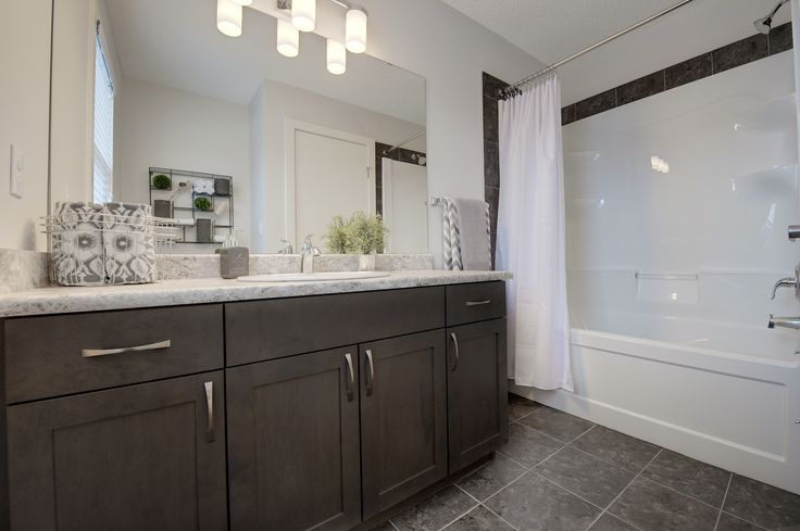 This master bedroom ensuite has a dark grey tile floor, stained maple cabinets, white laminate counter tops and sleek brushed chrome handles. The tub/shower unit has a tile surround and chrome finishings.