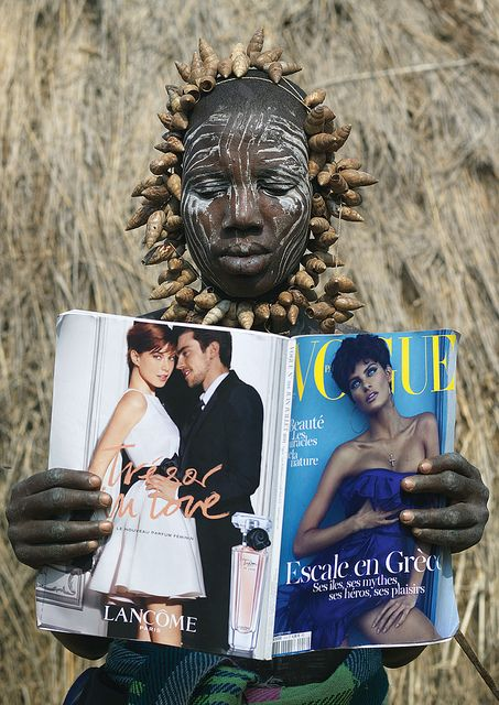 Mursi  Woman Reading Vogue Magazine - Omo Valley Ethiopia ~ 'Mursi have a lot of imagination to decorate themselves! They loved the magazine, ...'