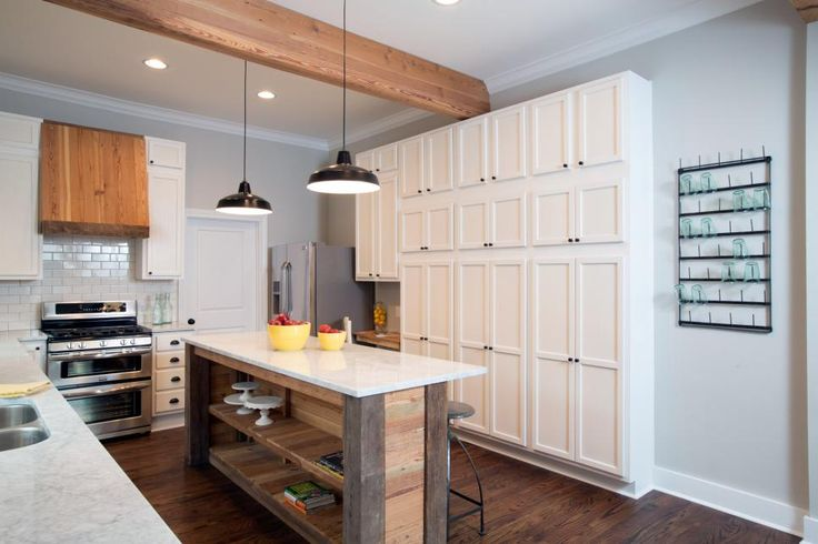 The island provides additional seating and open shelving. White cabinets spanning one wall and extending almost to the ceiling provide generous kitchen storage.