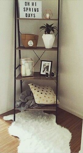shelf with bedding, plants, candles, picture frames.