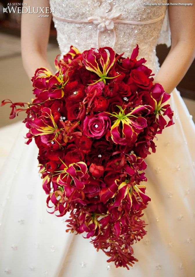 Stunning red and pink teardrop bouquet which includes roses, orchids and gloriosa.