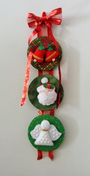 Noel, anjos e sinos compõem esse pingente que pode ser pendurado na porta, parede e aonde a imaginação mandar. Feito em feltro, tecido, fitas, botões e muitas cores. Cada bolacha mede 12 cm de diâmetro.