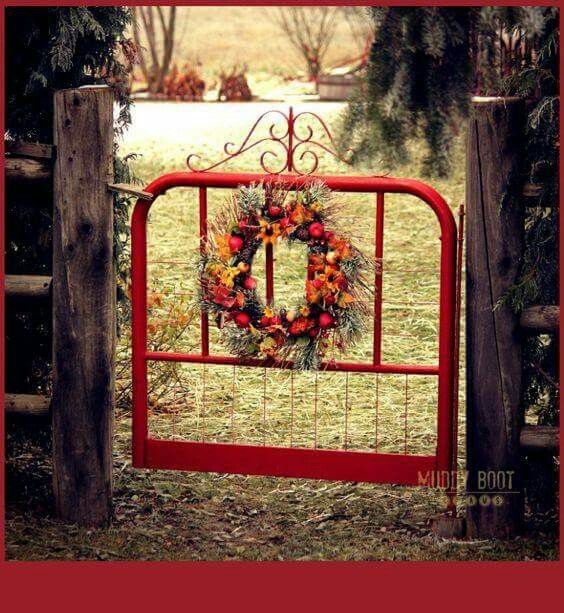 An old metal headboard is turned into a Beautiful red garden gate!