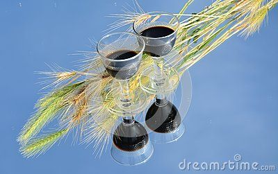 Two red wine glasses among wheat leaves reflected on the sky-like platform.