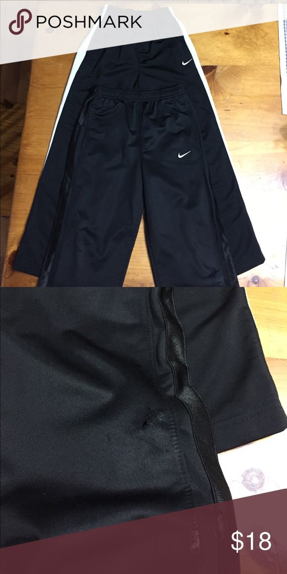 Nike Running Pants combo size 7 2 pair of boys Nike Running Pants size 7.  The solid black pair shows wear on the knees with small hole, see picture Nike Bottoms Sweatpants & Joggers