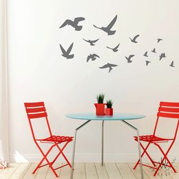 Gray flying bird wall stickers placed on a beige wall in flying formation behind a light blue modern small table and two red chairs. The birds appear to by flying towards a location together.