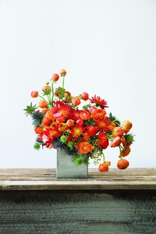 Whimsical centerpiece with bright orange floral by Dandelion Ranch ... image by Garden Design