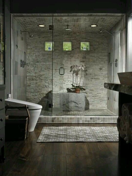 Central stone platform in narrow dual master shower w/ glass panel door.