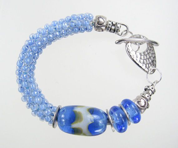 The bracelet is woven with light blue glass beads with three of my Lampwork beads added. I finished with a Silver toggle clasp. The bracelet is 7 inches long. If desired, I can increase the size of the bracelet by adding jump rings. Just let me know what size you would like. Thanks for looking, Kay