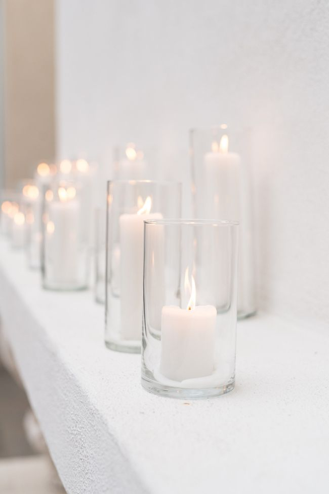 Candles in tall, cylindrical vases of clear glass create a simple, stunning ceremony backdrop for an All White Wedding:  http://www.confettidaydreams.com/all-white-wedding/ Pics: Monique Hessler Photography