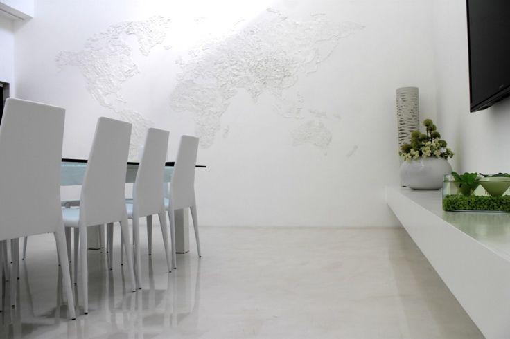 Lavorazione in resina decorativa che riproduce i dettagli di un planisfero, realizzata sulla parete verticale di un ambiente a uso civile.