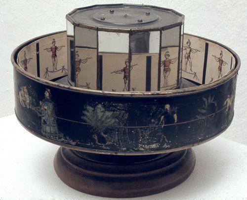 """19th Century Praxinoscope - Inventado pelo francês Émile Reynaud (1877), este brinquedo óptico surgiu do aperfeiçoamento do zootropo. A projecção é feita num espelho circular colocado no interior do """"tambor"""". Terá a vantagem de não cansar tanto o olho e de haver uma desfocagem menor do que é representado em animação. A multiplicação das figuras desenhadas e a adaptação de uma lanterna de projeção possibilitam a realização de truques que dão a ilusão de movimento."""