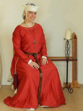 Hochmittelalter Kleid aus roter Seide. Kann wahlweise als Unter- oder Oberkleid getragen werden.   Alle sichtbaren Nähte und die Ziernaht am Kragen sind aus gelbem Leinen handgenäht.