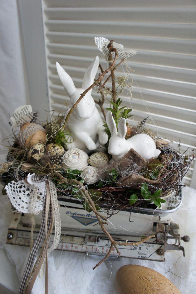 Eine zauberhaft schöne Osterdeko.... In einer antiken Küchenwaage sitzen ein kleiner und ein größerer Porzellanhase und wachen über das Ei im Nest... Es finden sich Wachteleier, Reben, Allerlei...