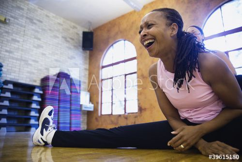 Woman stretching on floor while laughing